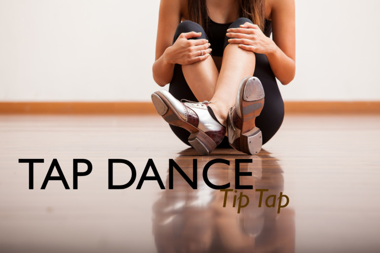 Closeup of the body of a dancer wearing tap shoes and taking a break in a studio